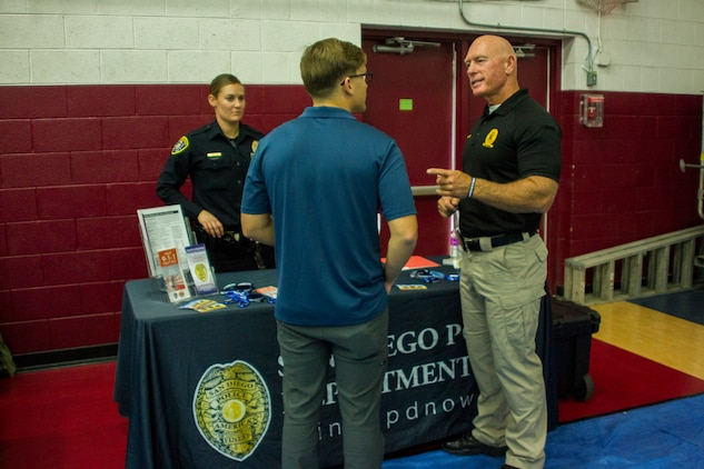 A Marine speaks to Steve Markland, police recruiter, Recruiting Unit, San Diego Police Department, about job opportunities with the department during the Education & Career Fair aboard the Marine Corps Air Ground Combat Center, Twentynine Palms, Calif., March 21, 2018. The Education & Career Fair is a tool for Marines looking to further their education, develop new skills and explore new career fields. (U.S. Marine Corps photo by Lance Cpl. Rachel K. Porter)