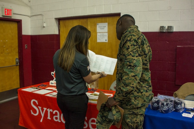 Jessica C. Calhoun, assistant director of student veteran and military admissions, Office of Admissions, Syracuse University, shows a Marine a catalog of courses that Syracuse offers during the Education & Career Fair aboard the Marine Corps Air Ground Combat Center, Twentynine Palms, Calif., March 21, 2018. The Education & Career Fair is a tool for Marines looking to further their education, develop new skills and explore new career fields. (U.S. Marine Corps photo by Lance Cpl. Rachel K. Porter)