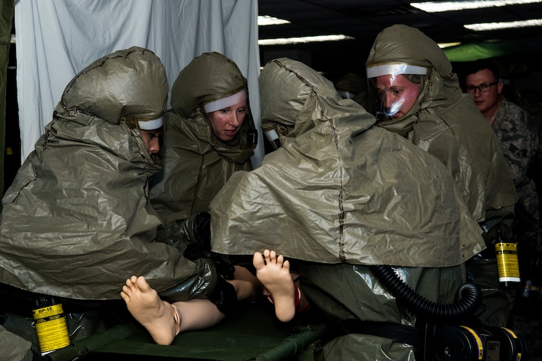 "Members from the 4th Medical Group Decontamination Team, process a simulated ""patient"" through the in-place patient decontamination tent, March 27, 2018, at Seymour Johnson Air Force Base, North Carolina."