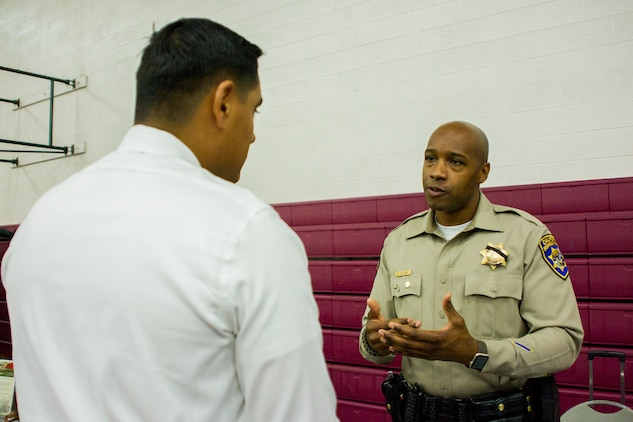 A Marine speaks to a California Highway Patrol officer about job opportunities during the Education & Career Fair aboard the Marine Corps Air Ground Combat Center, Twentynine Palms, Calif., March 21, 2018. The Education & Career Fair is a tool for Marines looking to further their education, develop new skills and explore new career fields. (U.S. Marine Corps photo by Lance Cpl. Rachel K. Porter)