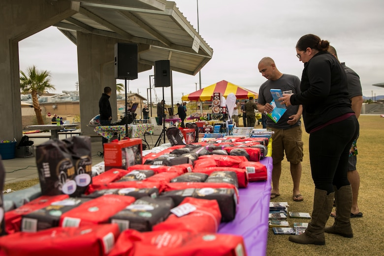 Marines, sailors and spouses of 1st Battalion, 7th Marine Regiment, look at raffle prizes during spring family day at Victory Field aboard the Marine Corps Air Ground Combat Center, Twentynine Palms, Calif., March 24, 2018. The unit family readiness officer hosts events like spring family day to enhance camaraderie, bring spouses together to form positive relationships and create activities for the children. (U.S. Marine Corps photo by Lance Cpl. Margaret Gale)