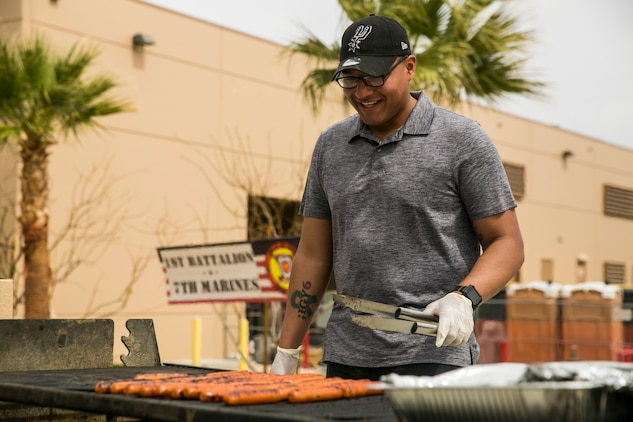Staff Sgt. Oscar Soto, battalion mess chief, 1st Battalion, 7th Marine Regiment, prepares hot dogs during a spring family day at Victory Field aboard the Marine Corps Air Ground Combat Center, Twentynine Palms, Calif., March 24, 2018. The unit family readiness officer hosts events like spring family day to enhance camaraderie, bring spouses together to form positive relationships and create activities for the children. (U.S. Marine Corps photo by Lance Cpl. Margaret Gale)