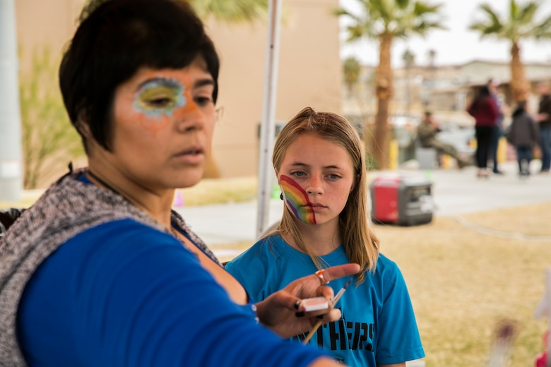 Skyler Sholl (right), 12, Combat Center patron, gets her face painted by Laura Rivas (left), special effects artist, during a spring family day at Victory Field aboard the Marine Corps Air Ground Combat Center, Twentynine Palms, Calif., March 24, 2018. The unit family readiness officer hosts events like spring family day to enhance camaraderie, bring spouses together to form positive relationships and create activities for the children. (U.S. Marine Corps photo by Lance Cpl. Margaret Gale)
