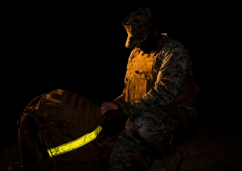 Gunnery Sgt. Jamal A. Russell, operations chief, Alpha Company, Headquarters Battalion, prepares his pack for a 6 mile company hike aboard the Marine Corps Air Ground Combat Center, Twentynine Palms, Calif., March 23, 2018. The Marines regularly conduct company level physical training events in order to maintain physical readiness for upcoming field operations. (U.S. Marine Corps photo by Lance Cpl. Jennessa Davey)