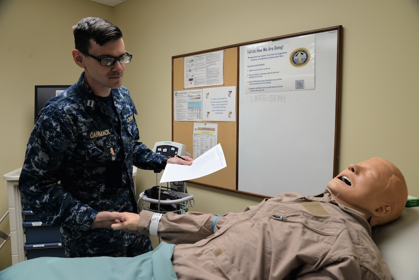 """U.S. Navy Lt. Jonathan Carmack, head of Naval Health Clinic Charleston's Staff, Education and Training Department, inspects a mock patient and its surroundings for potential hazards in NHCC's """"Room of Errors,"""" Mar. 16, 2018. The room was designed with purposely planted examples of hazards which could cause harm to patients or put their privacy at risk as part of Patient Safety Awareness Week, a national campaign which ran March 11-17."""