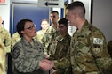 Chief Master Sgt. Amber Mitchell, 341st Missile Wing command chief, left, presents a coin to Airman Gideon Magrini, 841st Missile Security Forces Squadron missile security operator, Mar. 23, 2018, at Malmstrom Air Force Base, Mont.