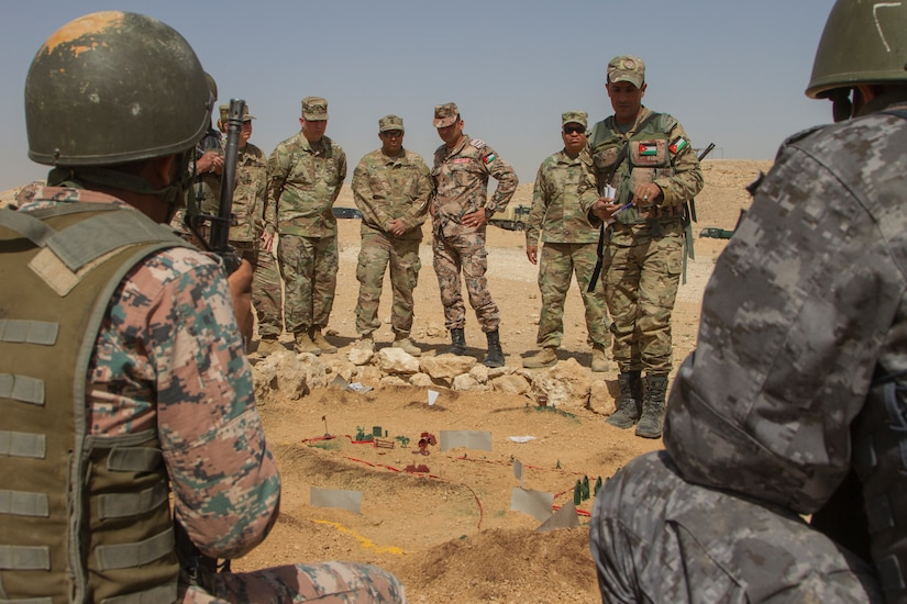 U.S. Soldiers from the 648th Military Engagement Team, Georgia Army National Guard, and instructors from the Jordan Armed Forces Noncommissioned Officer Academy receive a sand-table briefing during the JAF NCOA Squad Leader Course, near Amman, Jordan, March 18, 2018. The 648th MET advised JAF NCOA instructors as the Jordanian leaders developed the program of instruction for the course, which is attended by their soldiers and their regional allies. (U.S. Army photo by Sgt. Thomas X. Crough, USARCENT PAO)