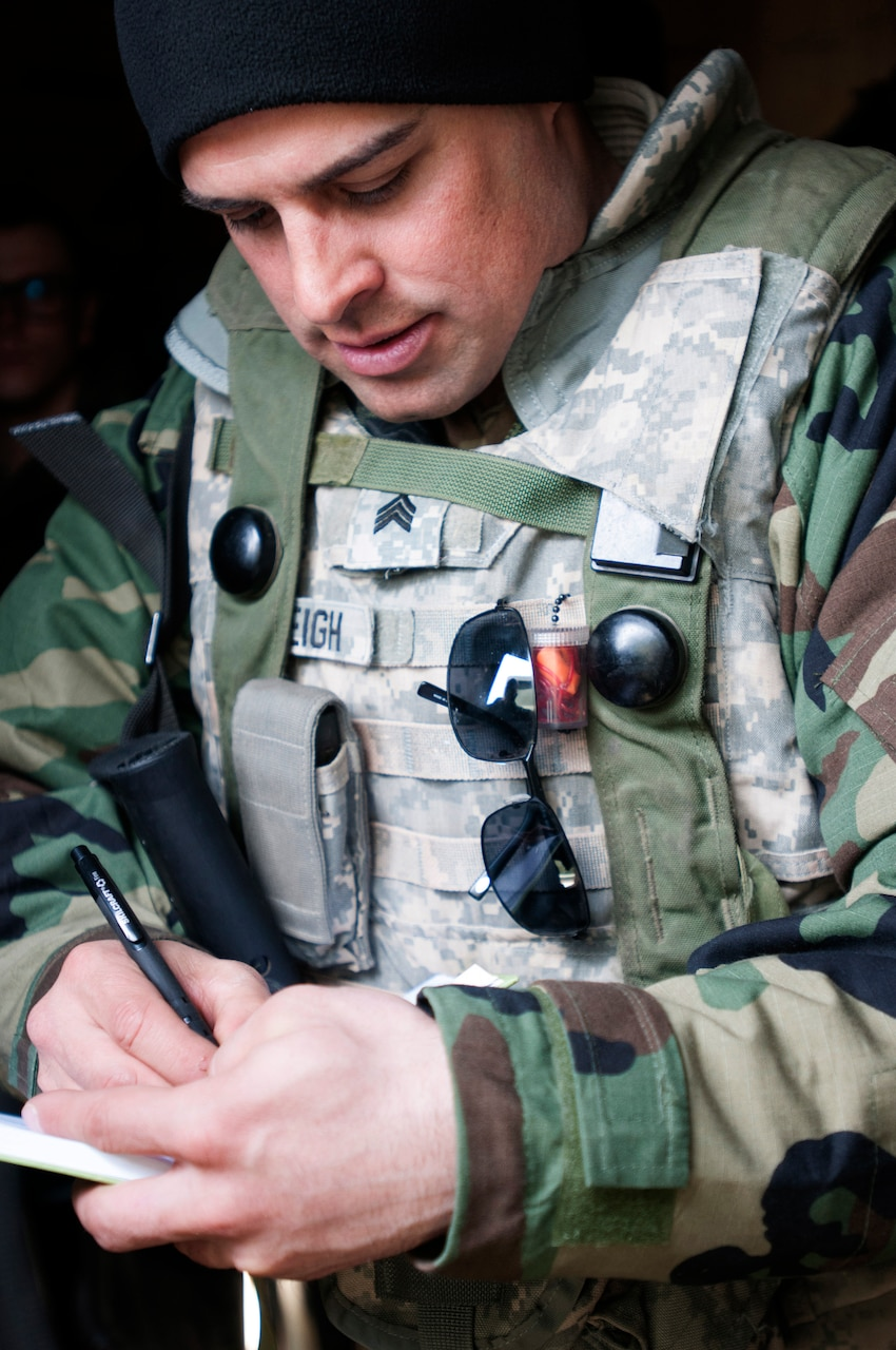A medic assigned to the Army Reserve's 256th Combat Support Hospital, headquartered in Twinsburgh, Ohio, fills in medical forms.