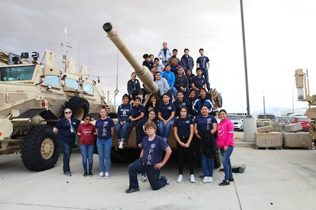 Students with the Desert Hot Springs High School Public Safety Academy pose with their teacher, Colleen Morgan, on a tank at the Exercise Support Division tactical vehicle lot at the culmination of their tour of Marine Corps Air Ground Combat Center, Twentynine Palms, Calif., March 22, 2018. The students are considering careers in the military or law enforcement. (U.S. Marine Corps photo by Kelly O'Sullivan)