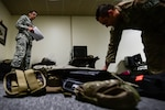 U.S. Air Force Staff Sgt. Justin Martinez, 20th Security Forces Squadron (SFS) unit deployment manager, left, inspects Senior Airman Michael Craig, 20th SFS installation patrolman, as he prepares a deployment bag at Shaw Air Force Base, S.C., March 29, 2018.