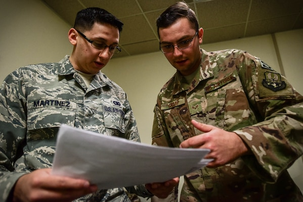 U.S. Air Force Staff Sgt. Justin Martinez, 20th Security Forces Squadron (SFS) unit deployment manager, left, and Senior Airman Michael Craig, 20th SFS installation patrolman, inspect a pre-deployment checklist at Shaw Air Force Base, S.C., March 29, 2018.