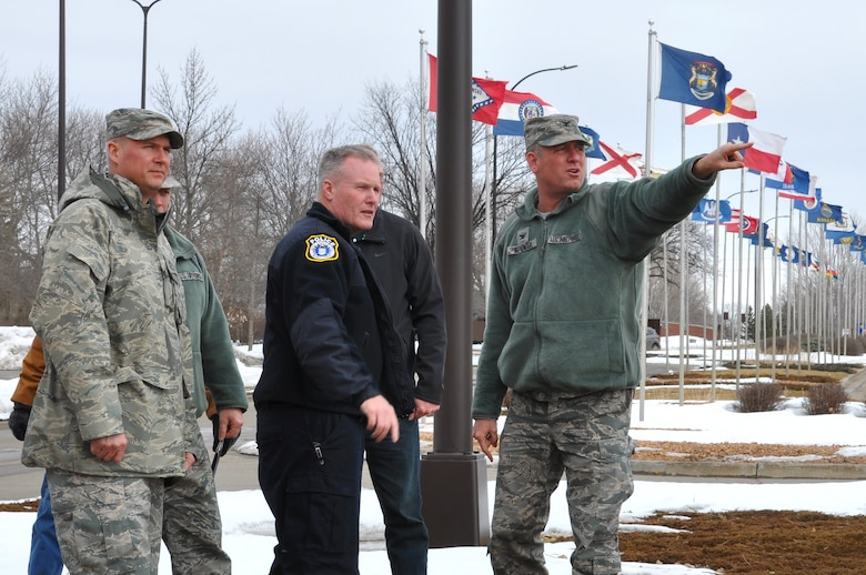 Col. Benjamin L. Spencer, 319th Air Base Wing commander (right), points to an area near the main gate to verify a location to be improved by scheduled construction March 28, 2018, at Grand Forks Air Force Base, N.D. The commander, along with the 319 ABW command chief, Chief Master Sgt. Brian Thomas (left), Terry Rutan, 319th Security Forces Squadron operations officer, and other subject matter experts surveyed security elements designed to prevent unauthorized entry to the installation. Construction on both installation gates is scheduled to start in April 2018 and includes many security upgrades. (U.S. Air Force photo by Master Sgt. Amanda Callahan)
