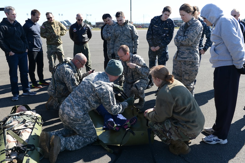 Washington National Guard crew chiefs assist Association of Military Osteopathic Physicians and Surgeons members to secure a simulated patient in a sked, March 10, 2018, at Joint Base Lewis-McChord, Wash. A sked is a tough plastic stretcher that can be used to move patients both on the ground and up to a hovering helicopter.  (U.S. Air Force photo by Airman 1st Class Sara Hoerichs)