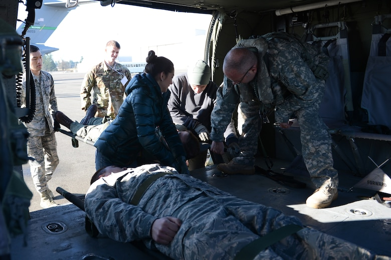 Army Sgt. Michael Cummings, Washington National Guard, Detachment 2, 168 General Support Aviation Battalion crew chief, assists members of the Association of Military Osteopathic Physicians and Surgeons load simulated patients into a UH-60 Black Hawk helicopter, March 10, 2018, at Joint Base Lewis-McChord, Wash. Crew chiefs are trained to assist medics during patient transport. (U.S. Air Force photo by Airman 1st Class Sara Hoerichs)