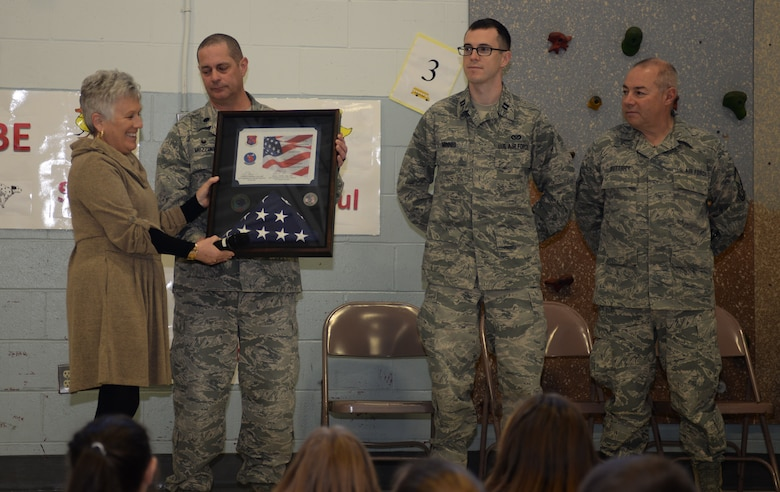 Michelle McAlister, principal for the McClelland Elementary School, accepts a flag and certificate from Lt. Col. Eugene R. Mozzoni, commander of the 157th Civil Engineering Squadron, Captain Erik Minnis and Chief Master Sgt. Todd Buttick, New Hampshire Air National Guard, during a ceremony thanking the students for sending letters to the 157th Civil Engineer Squadron while the unit was deployed to the middle east over the 2017 holiday season, March 27, 2018, Rochester, N.H.  The flag was flown over the country of Kuwait during Christmas while the squadron was deployed there. (N. H. Air National Guard photo by Master Sgt. Thomas Johnson)
