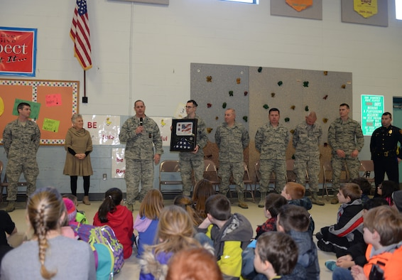 Lt. Col. Eugene R. Mozzoni, 157th Civil Engineering Squadron commander, thanks students of the McClelland Elementary School during a brief ceremony thanking the students for sending letters to the 157th Civil Engineering Squadron while they were deployed to the middle east over the past holiday season. March 27, 2018, Rochester, N.H.  The flag was flown over the country of Kuwait during Christmas while the squadron was deployed there. (N. H. Air National Guard photo by Master Sgt. Thomas Johnson)