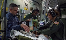 59th Medical Wing Critical Care Air Transport Team members, along with the patient's father, entertain an infant during an air transport mission from Germany to Walter Reed National Medical Center, Bethesda, Md., April 19th, 2018. CCATT teams maintain the standard of care provided to critically ill, injured or burned patients who require continuous stabilization and advanced care during transport to the next level of care. (U.S. Air Force photo by Senior Airman Keifer Bowes)