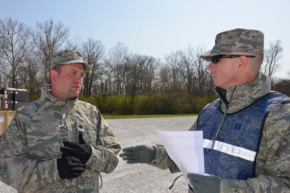 Capt. Lee Laughridge, (right) chief, Air Forces Northern  Medical Operations and Training, talks with Lt, Col. Randall Shiflett 81st Medical Group medical control center team chief, about the daily operations situational report Shiflett submitted during the Expeditionary Medical Support field confirmation exercise here April 18. The confirmation exercise is evaluating the tactics, techniques and procedures of EMEDS operations during a domestic U.S. contingency such as a natural disaster. (Air Force photo by Mary McHale)