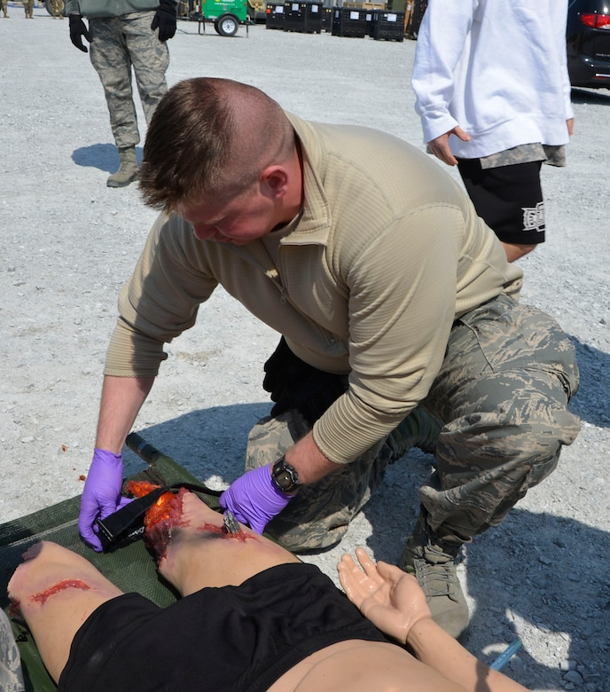 "Senior Airman Glen Snyder, 81st Medical Group medic, Keesler Air Force Base, Miss., applies a tourniquet to a simulated  ""resident"" injured in the natural disaster tornado scenario during the Expeditionary Medical Support field confirmation exercise here April 18. The confirmation exercise is evaluating the tactics, techniques and procedures of EMEDS operations during a domestic U.S. contingency such as a natural disaster. (Air Force photo by Mary McHale)"