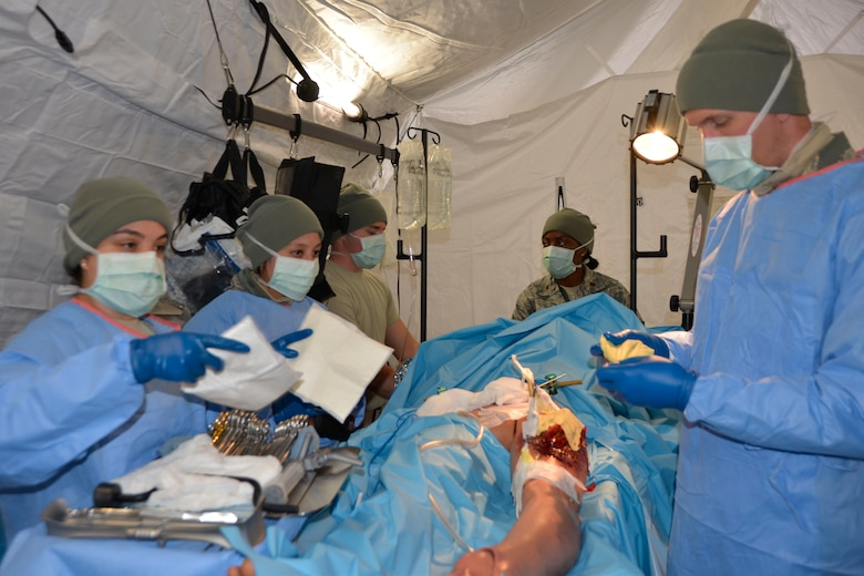 Staff Sgt. Luiza Pereira, surgical technician, 81st Medical Group, Keesler Air Force Base, Miss., hands a gauze dressing to Maj. (Dr.) T. David Tarity, 81st MDG, during an emergency surgery procedure on a natural disaster tornado scenario victim. The procedure was part of the ongoing Expeditionary Medical Support field confirmation exercise here April 18. The confirmation exercise is evaluating the tactics, techniques and procedures of EMEDS operations during a domestic U.S. contingency such as a natural disaster. (Air Force photo by Mary McHale)
