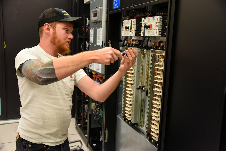 Ridge Yadori, a Lockheed Martin field technician, installs circuit breakers into one of two new F-35 simulator power distribution units