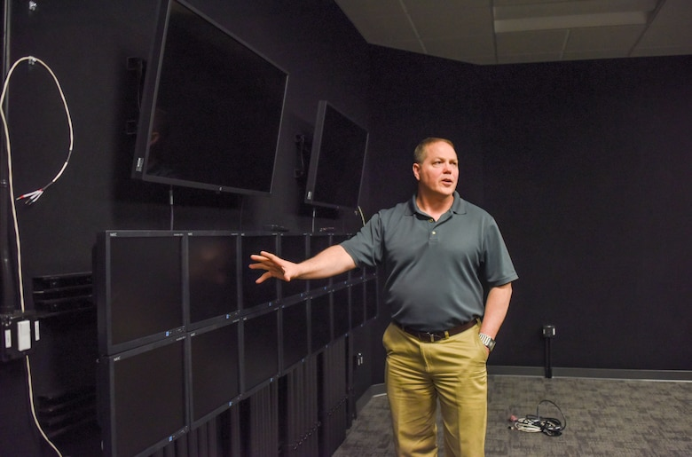 Nathan Hill, the Lockheed Martin F-35 Training Systems Manager for the simulators at Hill Air Force Base, Utah, showcases multiple display screens in a debrief room