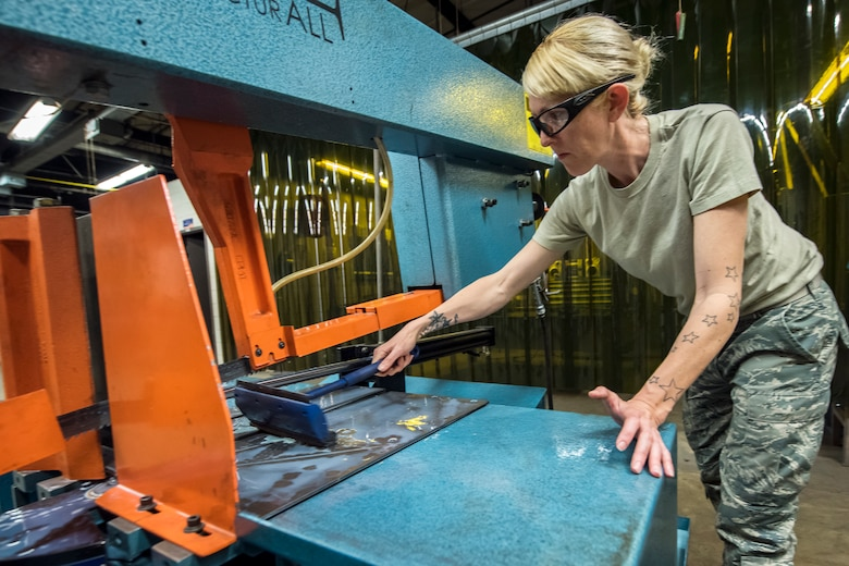 Tech. Sgt. Anna Gee, 476th Maintenance Squadron metals technology shop chief, cleans a horizontal band saw, April 25, 2018, at Moody Air Force Base, Ga. Metals technicians support the mission by utilizing fabrication techniques to repair and overhaul countless tools and aircraft parts. The technicians strive to exercise safe and precise fabrication techniques to be able to sufficiently handle their intense workload. (U.S. Air Force photo by Airman 1st Class Eugene Oliver)