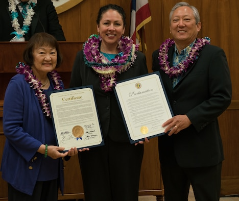 (Center) Dr. Lisa Charles, Pacific Air Forces Sexual Assault Prevention and Response Program Manager, receives a certificate and proclamation from (left) Ann Kobayashi, Honolulu City Council member, and (right) Roy Amemiya, Honolulu city managing director, at Honolulu City Hall April 18, 2018.