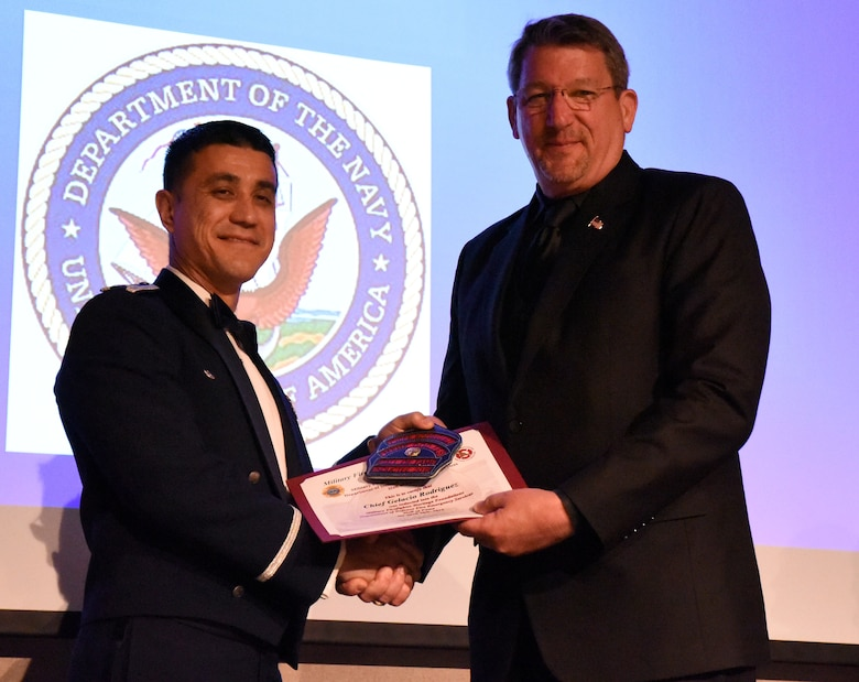 U.S. Air Force Col. Ricky Mills, 17th Training Wing commander, presents Chief Gene Rausch, guest of honor, with a clip for a firefighter helmet as congratulations during the 16th Annual Firefighter Ball at the McNease Convention Center, San Angelo, Texas, April 28, 2018. The hall of fame inductee award is intended for Chief Gelacio Rodriquez, firefighter hall of fame inductee, who could not attend the ball. (U.S. Air Force photo by Airman 1st Class Seraiah Hines/Released)