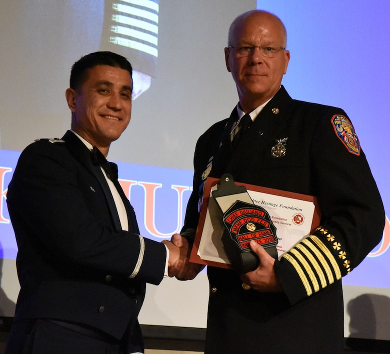 U.S. Air Force Col. Ricky Mills, 17th Training Wing commander, congratulates Chief Mark Guiliano, on receiving the Lifetime Achievement Award and being inducted into the Hall of Fame during the 16th Annual Firefighter Ball at the McNease Convention Center, San Angelo, Texas, April 28, 2018. Guiliano started his career in 1978 as an Air Force firefighter and crossed into the civilian sector in 2001. (U.S. Air Force photo by Airman 1st Class Seraiah Hines/Released)
