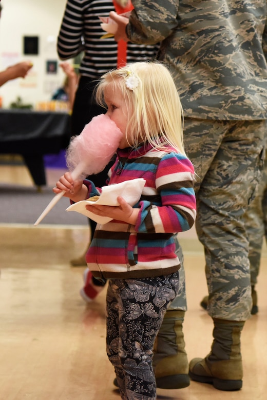 Eliana Swaim, daughter of Capt. Jessica Swaim, 436th Medical Support Squadron logistics flight commander, enjoys cotton candy during the Deployed Families Dinner April 19, 2018, at Dover Air Force Base, Del. The carnival-themed event featured several treats, including cotton-candy, snow cones and pop-corn. (U.S. Air Force photo by Airman 1st Class Zoe M. Wockenfuss)