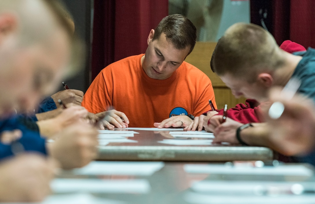 Capt. Curtis Billig, 9th Airlift Squadron C-5M Super Galaxy pilot, takes a written test about Air Force history April 27, 2018, at the Base Theater on Dover Air Force Base, Del. One individual from each of the 23 teams competing in the Wingman Day Amazing Race had to answer every question correctly in order to receive a clue that would lead their team to the next destination. (U.S. Air Force photo by Roland Balik)