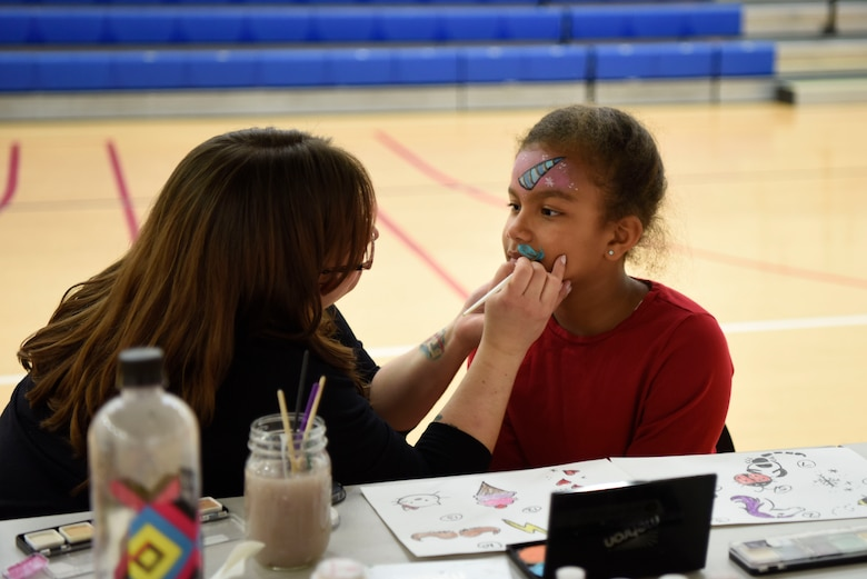 Aarilyn Brown, daughter of 1st Sgt. Sharry Barnshaw, 3rd Airlift Squadron first sergeant, gets her face painted by a volunteer during the Deployed Families Dinner April 19, 2018, at Dover Air Force Base, Del. In addition to face painting, corn-hole, a photo booth and two bounce houses were provided for the families. (U.S. Air Force photo by Airman 1st Class Zoe M. Wockenfuss)