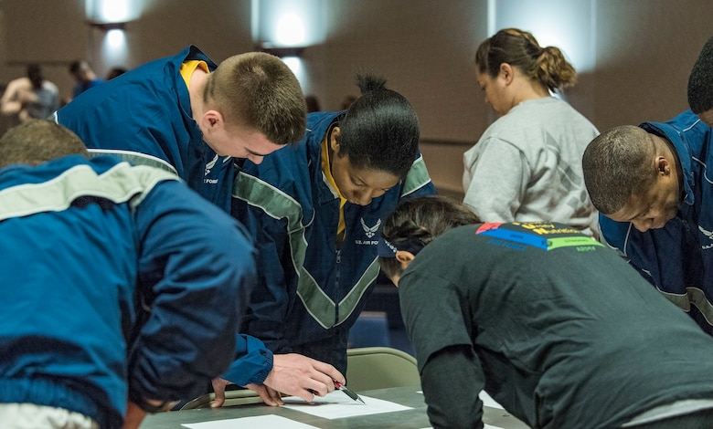 During their first challenge, Wingman Day Amazing Race team members work together answering Air Force history questions before receiving their first clue April 27, 2018, at the base theater on Dover Air Force Base, Del. If needed, teams were allowed to use help from a teammate to answer questions correctly. (U.S. Air Force photo by Roland Balik)