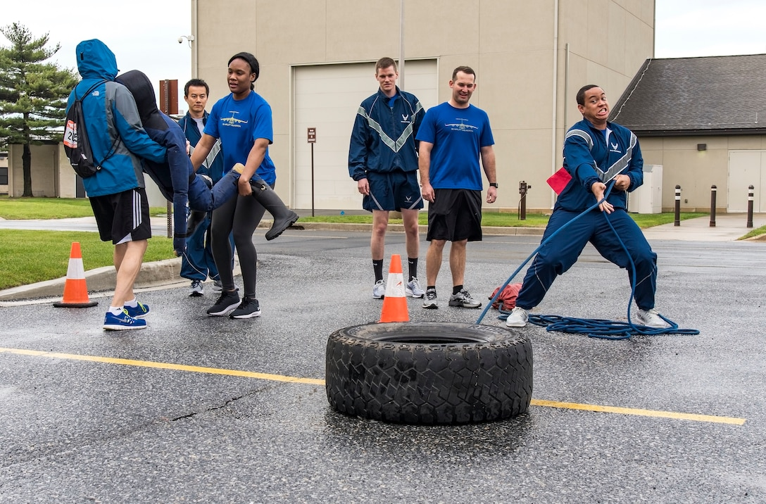 Amazing Race team members from the 3rd Airlift Squadron engage in two of the five designated challenges during Wingman Day April 27, 2018, at the fire department on Dover Air Force Base, Del. Each Amazing Race team included at least one Airman, NCO, senior NCO and an officer. Civilians and spouses were also encouraged to join their unit's team. (U.S. Air Force photo by Roland Balik)