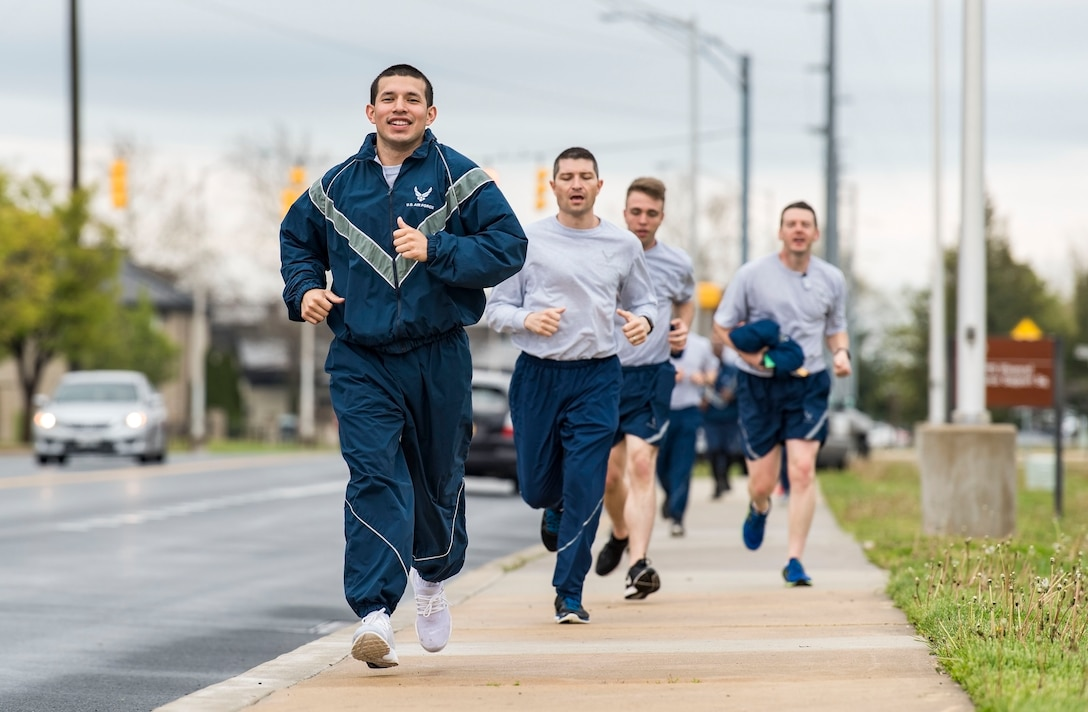 Staff Sgt. Jose Marroquin, 436th Maintenance Group maintenance analyst, leads his Wingman Day Amazing Race team as they run to their next challenge location April 27, 2018, on Dover Air Force Base, Del. Upon completing each challenge, teams were given a clue instructing them to proceed to one of 10 designated Amazing Race locations. (U.S. Air Force photo by Roland Balik)