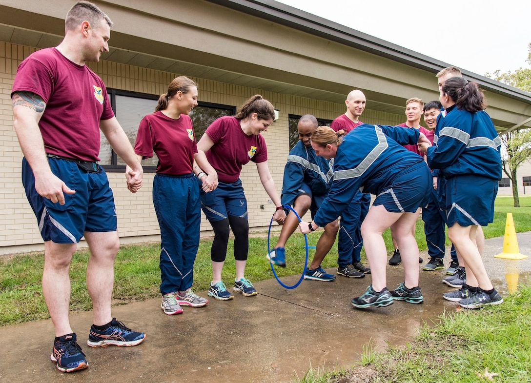 While holding hands, 10 team members from the 436th Medical Operations Squadron thread themselves through a hoop during one of many Wingman Day Amazing Race team challenges April 27, 2018, on Dover Air Force Base, Del. After the first person in the chain cleared the hoop, her left hand was used to guide the hoop through her remaining nine teammates. (U.S. Air Force photo by Roland Balik)