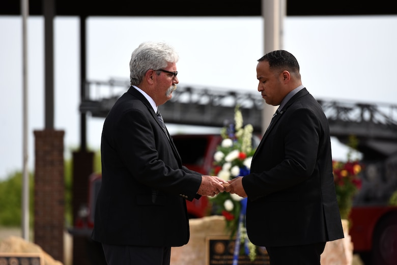 President of the Military Firefighter Heritage Foundation, Mike Robertson, presents U.S. Army Safety and Fire Emergency Services Program Manger Chief A.J. Eversley, with a plaque in honor of firefighter Chief Charles Crist at the Fallen Department of Defense Firefighter Memorial ceremony on Goodfellow Air Force Base, Texas, April 27, 2018. Crist died of a heart attack Feb. 26, 1967 after returning from an emergency. (U.S. Air Force photo by Airman 1st Class Seraiah Hines/ Released)