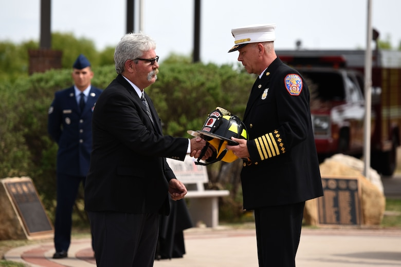 President of the Military Firefighter Heritage Foundation, Mike Robertson, presents Chief Mark Guiliano, Fire Emergency Services Flight, 96 Civil Engineer Squadron, Eglin Air Force Base, Florida, with a firefighter helmet in honor of Assistant Chief Edward Vanner at the Fallen Department of Defense Firefighter Memorial ceremony on Goodfellow Air Force Base, Texas, April 27, 2018. Vanner was a member of the Rhode Island Air National Guard 143rd Airlift Wing before passing away June 17, 2017. (U.S. Air Force photo by Airman 1st Class Seraiah Hines/Released)