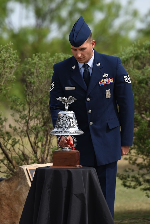 U.S. Air Force Staff Sgt. Alexander Spears, 312th Training Squadron instructor, rings the bell three times, three times in a row at the Fallen Department of Defense Firefighter Memorial ceremony on Goodfellow Air Force Base, Texas, April 27, 2018. The ringing of the bell in this pattern symbolizes a fallen firefighter's duties are over and the still living will take on the duty of protecting those left behind. (U.S. Air Force photo by Airman 1st Class Seraiah Hines/Released)
