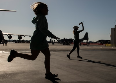 A child chases down a paper airplane during a paper-plane-throwing competition at the Air and Space Expo at Joint Base Charleston, S.C.