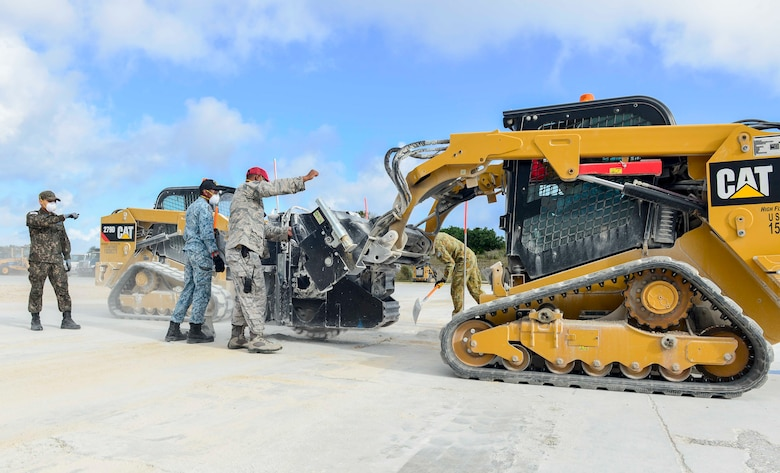 A member of the 554th RED HORSE Squadron, center, guides wingmen of the Republic of Korea Air Force and Republic of Singapore Air Force during the use of a compact track loader saw cutter as part of a training task of exercise Silver Flag April 24, 2018, at Northwest Field, Guam. Teams faced a simulated aftermath of a base attack. They had to repair facilities and the airfield to ensure that they can get the airfield back up and operational. (U.S. Air Force by Airman 1st Class Christopher Quail)