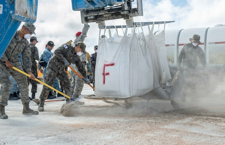 Airmen of the Royal Australian Air Force, Republic of Korea Air Force, Republic of Singapore Air Force and U.S. Air Force fill concrete mix into a hole during exercise Silver Flag, at Northwest Field, Guam, April 24, 2018. Teams faced a simulated aftermath of a base attack and having to repair facilities and the airfield to ensure that they can repair the airfield and return it to safe use for aviators. (U.S. Air Force by Airman 1st Class Christopher Quail)