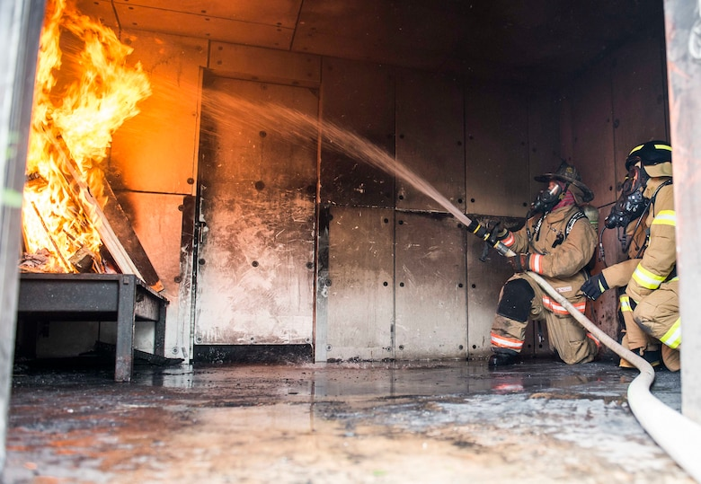 U.S. Air Force and Republic of Korea Air Force firefighters extinguish a training building fire during exercise Silver Flag April 24, 2018, at Northwest Field, Guam. The weeklong exercise is designed to build partnerships and promote interoperability through the exchange of civil engineer-related information. (U.S. Air Force by Airman 1st Class Christopher Quail)
