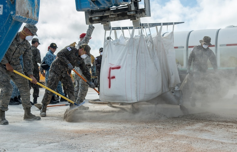 U.S. Air Force Airmen, Royal Australian Air Force, Republic of Korea Air Force, and Republic of Singapore Air Force fillconcrete mix into a hole during Silver Flag April 24, 2018, at Northwest Field, Guam. Teams faced a simulated aftermath of a base attack and having to repair facilities and the airfield to ensure that they can get the airfield back up and operational. (U.S. Air Force by Airman 1st Class Christopher Quail)