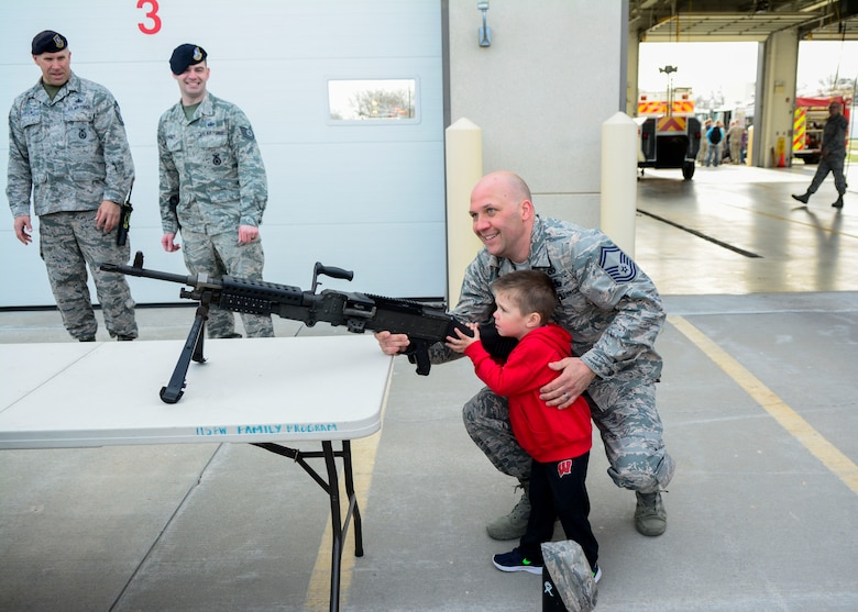 Jason Kasten, a host aviation resource manager with the 115th Operations Support Squadron, and his son Jordy Kasten hold an M249 light machine gun during National Take Our Daughters and Sons to Work Day April 26, 2018.  (U.S. Air National Guard photo by Cameron R. Lewis)