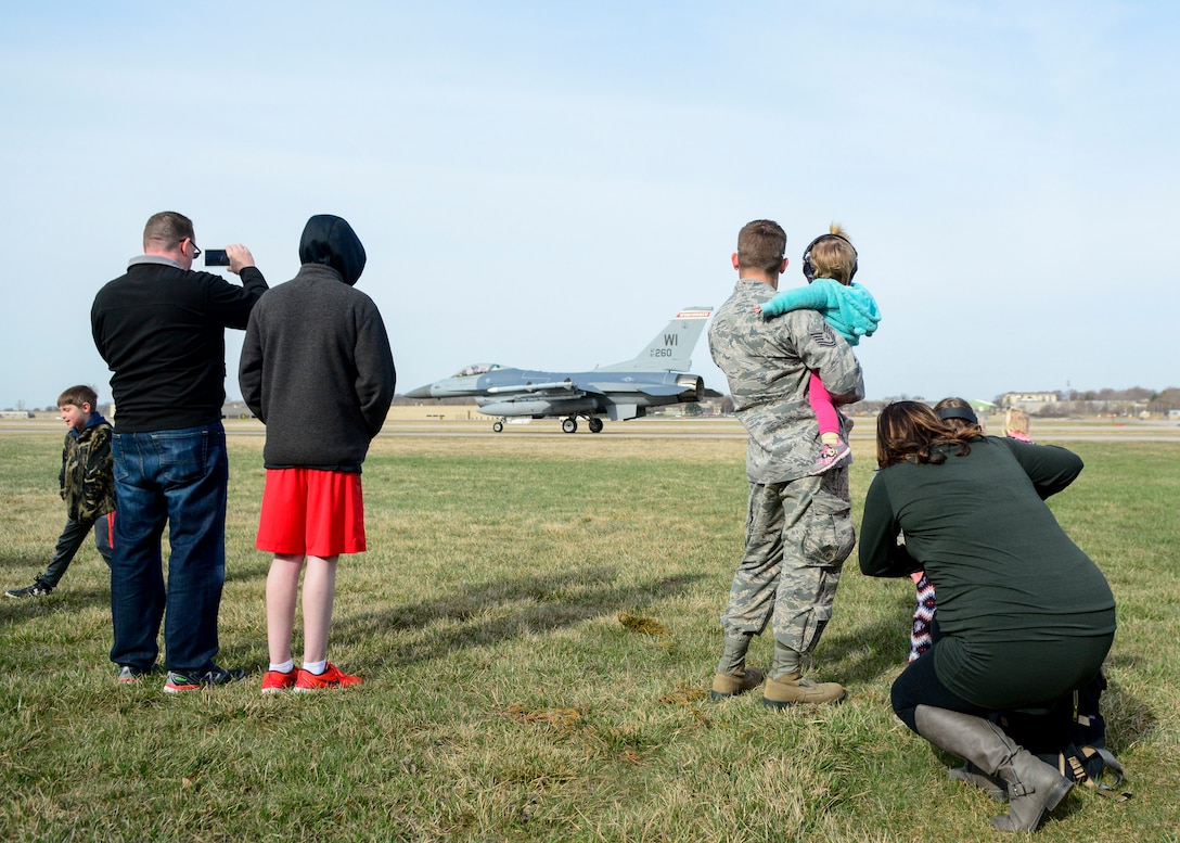 Airmen and their families watch as an F-16 Fighting Falcon prepares for takeoff April 26, 2018 at Truax Field, Wis. This was one of many demonstrations put on by the 115th Fighter Wing for National Take Our Daughters and Sons to Work Day. (U.S. Air National Guard photo by Mary Greenwood)