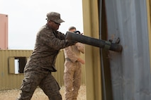 A member of the Tunisian Army Quick Reaction Force breaks down a door during Exercise African Lion 2018, in Tifnit, Morocco, April 20, 2018. African Lion is an annual, multinational, joint-force exercise improving interoperability between participating nations. (U.S. Marine Corps photo by Lance Cpl Tessa D. Watts)
