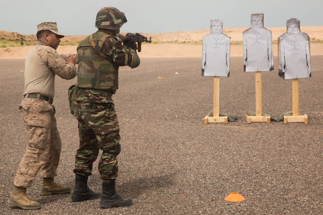 U.S. Marine Lance Cpl. Bryan Verduzco, infantry team leader with Fleet Antiterrorism Security Team, guides a member of Gendarmerie through speed reload training during Exercise African Lion 2018, in Tifnit, Morocco April 20, 2018. African Lion is an annual, multinational, joint-force exercise improving interoperability between participating nations. (U.S. Marine Corps photo by Lance Cpl Tessa D. Watts)