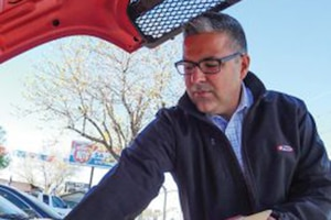 A man looks under the hood of a car.